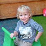 blonde boy at preschool on green tractor
