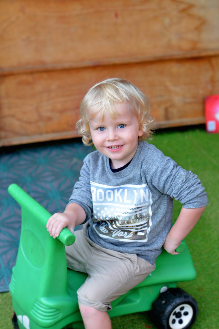 blonde boy at preschool on green tractor